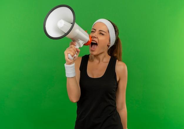 녹색 벽 위에 서있는 적극적인 표현으로 확성기로 외치는 머리띠와 스포츠웨어에 젊은 피트 니스 여자