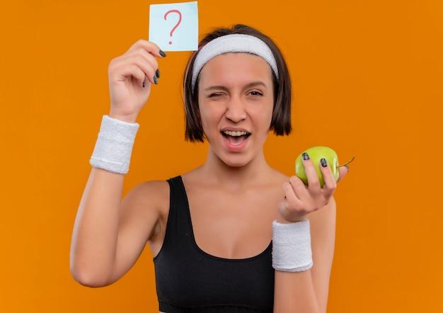 녹색 사과 윙크를 들고 오렌지 벽에 서 행복 한 얼굴로 웃 고 물음표와 알림 종이를 보여주는 머리띠와 스포츠웨어에 젊은 피트 니스 여자