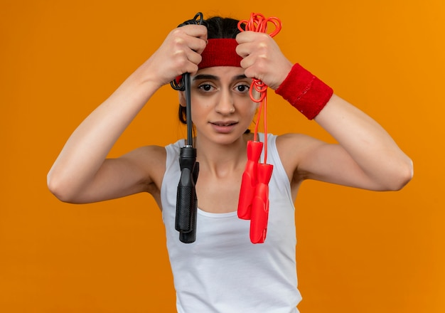 オレンジ色の壁の上に立っている疑いを持って混乱しているように見える2本の縄跳びを示すヘッドバンドを持つスポーツウェアの若いフィットネス女性