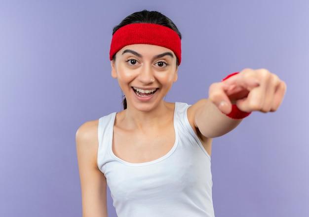 紫色の壁の上に立っているカメラに人差し指で元気に指して笑顔のヘッドバンドとスポーツウェアの若いフィットネス女性