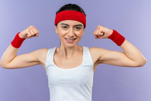 紫色の壁の上に幸せで前向きに立っている上腕二頭筋を示す元気に拳を上げて笑っているヘッドバンドとスポーツウェアの若いフィットネス女性