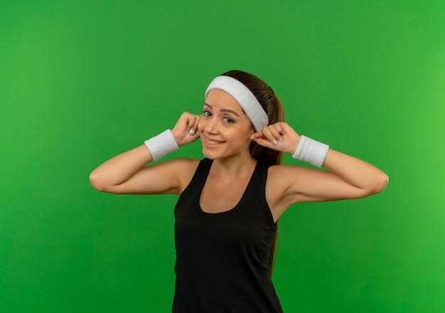緑の壁の上に立っている彼女の耳を元気に見せて笑顔のヘッドバンドとスポーツウェアの若いフィットネス女性