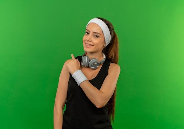 緑の壁の上に立って指を後ろに向けて自信を持って笑顔のヘッドバンドとスポーツウェアの若いフィットネス女性