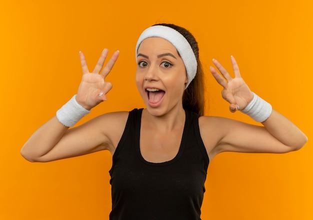 오렌지 벽 위에 서 행복하고 긍정적 인 표시 확인 기호를 보여주는 머리띠와 운동복에 젊은 피트 니스 여자