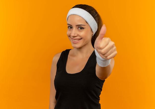 오렌지 벽 위에 서서 행복하고 긍정적 인 보여주는 엄지 손가락을 웃는 머리띠와 운동복에 젊은 피트 니스 여자