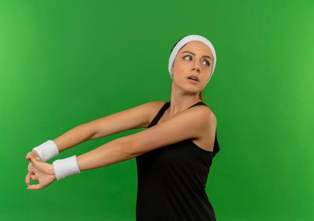 녹색 벽 위에 자신감 서 찾고 자신을 스트레칭 머리띠와 스포츠웨어에 젊은 피트 니스 여자