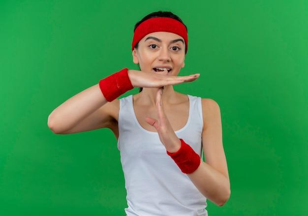 Молодая фитнес-женщина в спортивной одежде с повязкой на голову удивлена, делая жест тайм-аута с руками, стоящими над зеленой стеной