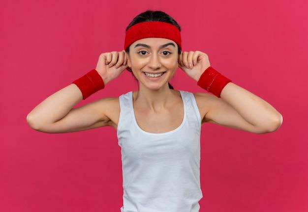 핑크 벽 위에 서있는 얼굴에 큰 미소로 그녀의 귀를 만지고 머리띠와 스포츠웨어에 젊은 피트 니스 여자