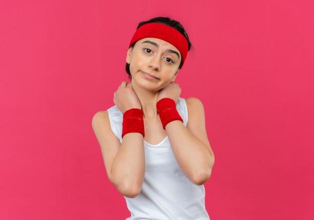 ピンクの壁の上に立って不快感を感じて彼女の首にヘッドバンドが触れているスポーツウェアの若いフィットネス女性