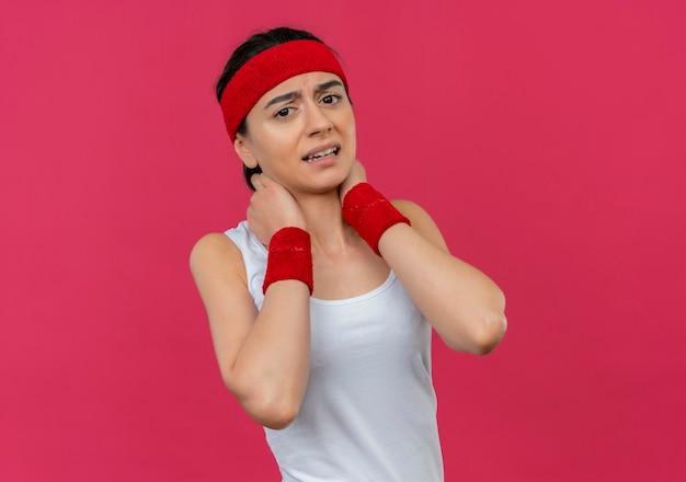 ピンクの壁の上に立っている痛みを感じて不快なヘッドバンドが首に触れているスポーツウェアの若いフィットネス女性