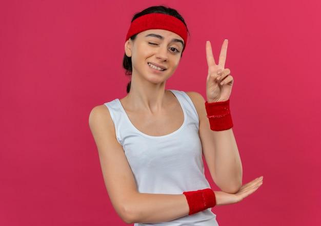 ピンクの壁の上に立っている勝利のサインを示すヘッドバンドのウィンクと笑顔でスポーツウェアの若いフィットネス女性