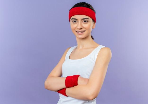 紫色の壁の上に立って自信を持って笑って胸に腕を組んでヘッドバンドとスポーツウェアの若いフィットネス女性