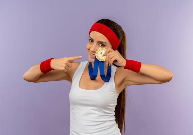Молодая фитнес-женщина в спортивной одежде с повязкой на голову с золотой медалью на шее показывает и указывая пальцем на нее, улыбаясь, стоя над серой стеной