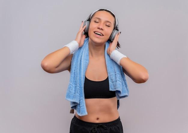 頭にヘッドフォンと首にタオルを持ったスポーツウェアの若いフィットネス女性は、白い壁の上に立って目を閉じてお気に入りの音楽を楽しんでいます