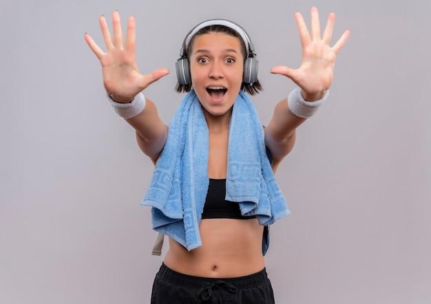 頭にヘッドフォンと首にタオルを持ったスポーツウェアの若いフィットネス女性が手のひらを差し出し、白い壁の上に立って幸せで興奮している10番の笑顔を示しています