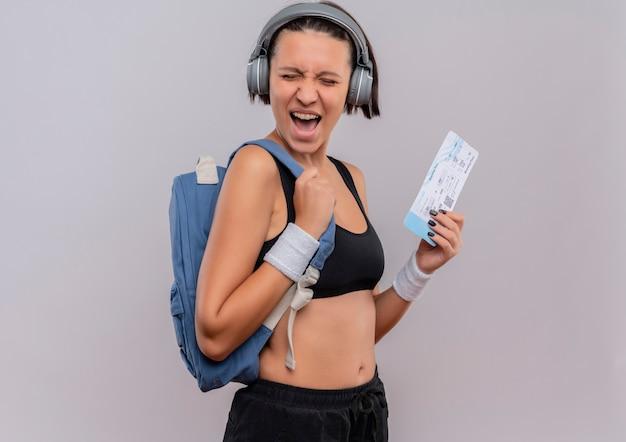 흰 벽 위에 서있는 항공 티켓 미친 행복 소리를 들고 배낭 머리에 헤드폰으로 운동복에 젊은 피트 니스 여자