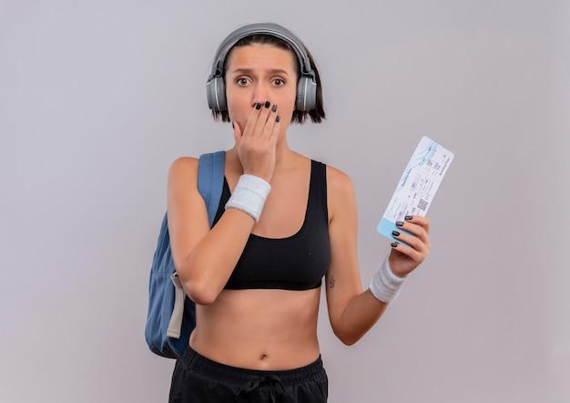 배낭에 항공 티켓을 들고 머리에 헤드폰으로 운동복에 젊은 피트 니스 여자는 흰 벽 위에 서 손으로 입을 덮고 충격