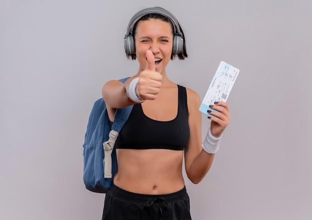 흰색 벽 위에 서 엄지 손가락을 보여주는 항공 티켓을 들고 배낭 머리에 헤드폰으로 운동복에 젊은 피트 니스 여자