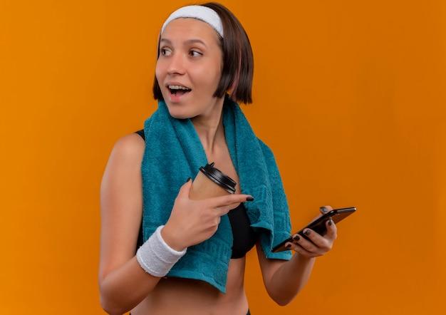 コーヒーカップとスマートフォンを持って首にタオルを持ったスポーツウェアの若いフィットネス女性がオレンジ色の壁の上に元気に立って笑って脇を見て