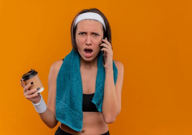 オレンジ色の壁の上に立っている積極的な表情で携帯電話で話しているコーヒーカップを保持している彼女の首にタオルでスポーツウェアの若いフィットネス女性