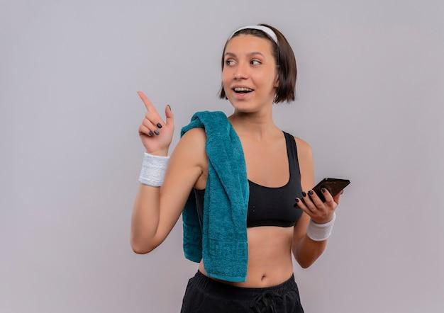 白い壁の上に元気に立って笑って横に指で指しているスマートフォンを保持している肩にタオルでスポーツウェアの若いフィットネス女性