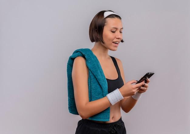 白い壁の上に立っている顔に笑顔で彼女の携帯電話の画面を見て肩にタオルでスポーツウェアの若いフィットネス女性