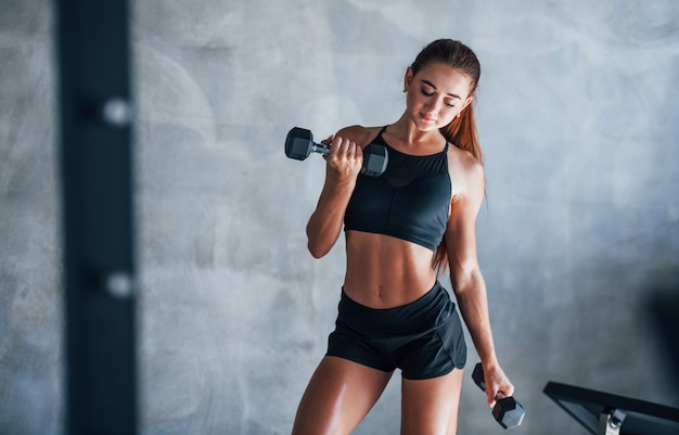 Young fitness woman is in the gym with dumbbells in hands.