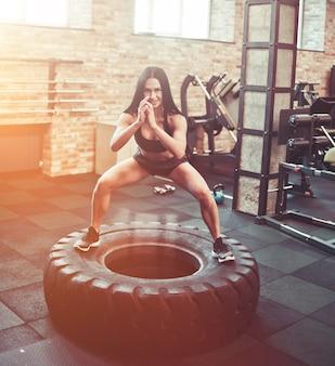 ジムで大きなホイールに飛び出す若いフィットネス女性。ファンクショナルトレーニング