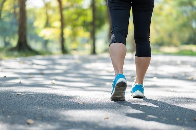 屋外の公園で歩く若いフィットネスの女性の足