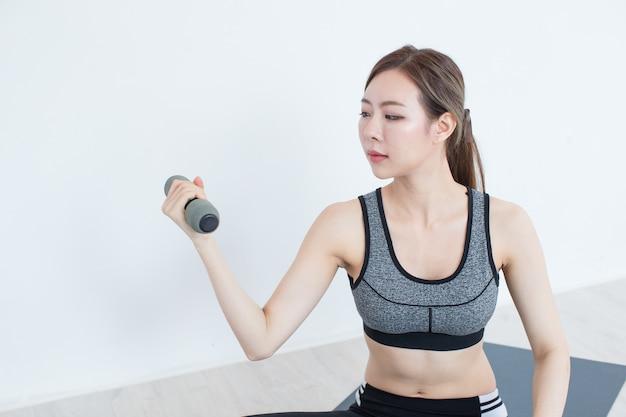 Молодая женщина фитнеса подъема гантелей