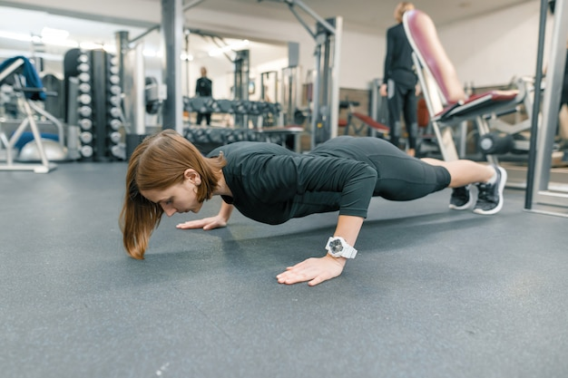 Young fitness woman making push-up exercises in gym