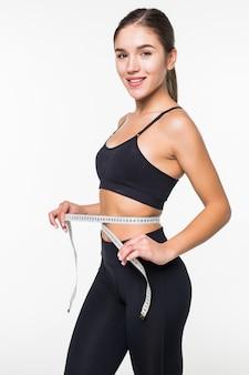 Молодая женщина фитнес измерения с лентой ее живот, изолированные на белой стене