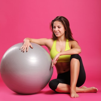 Young and fitness woman on pink