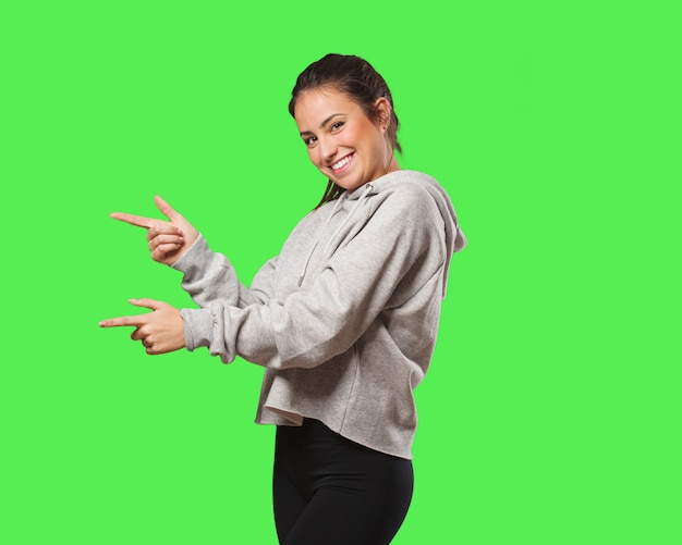 Young fitness woman pointing to the side with finger