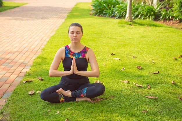 Young fitness woman practicing yoga in park, lotus pose. healthy, active lifestyle, sport, yoga theme.