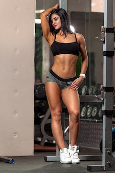 Young fitness woman pulls up in the gym brunette fitness woman in sport wear with perfect muscular body