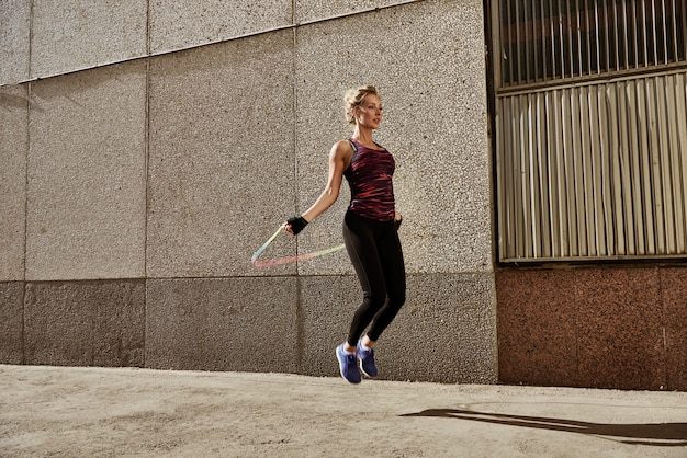 Young fitness woman rope skipping against city wall.
