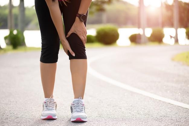 若いフィットネス女性ランナーは、公園で彼女の膝の痛みを感じます。