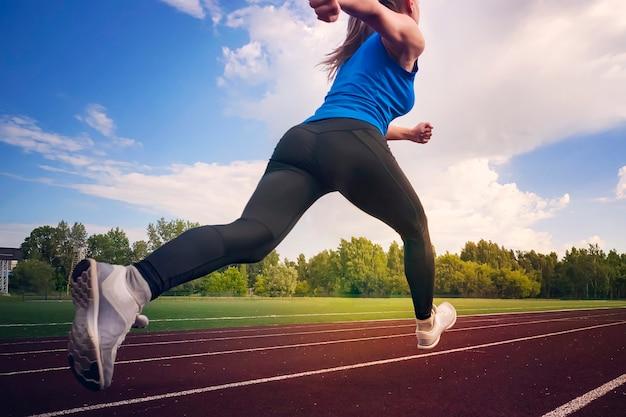 경기장 트랙에서 실행 하는 젊은 피트 니스 여자 주자입니다. 비행 중 점프의 시간. 체육 실기. 건강한 생활 방식과 스포츠의 개념. 배면도.