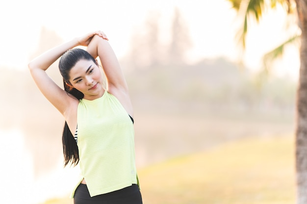 公園で走る前にストレッチする若いフィットネス女性ランナー