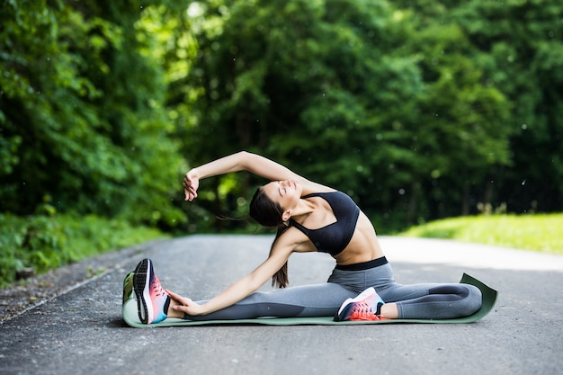 Young fitness woman runner stretching legs before run in the city park