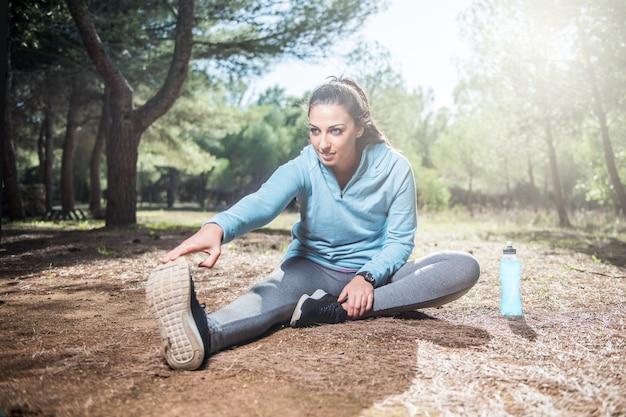 公園で実行する前に足を伸ばす若いフィットネス女性ランナー