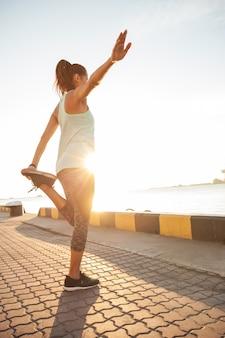 항구 근처 도시에서 달리기 전에 다리를 쭉 뻗는 젊은 피트니스 여성 주자