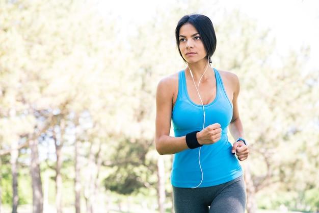屋外で走っている若いフィットネス女性