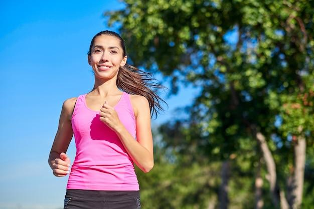 森の小道で走っている若いフィットネス女性。