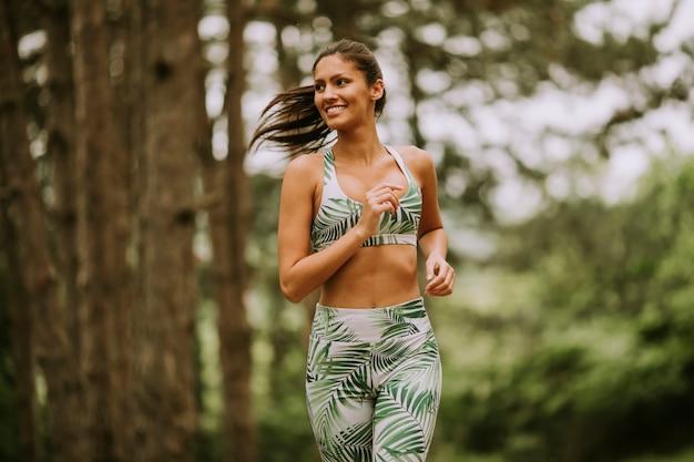 森林歩道で走っている若いフィットネス女性