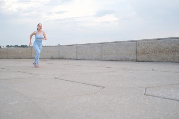 도시에서 실행 하는 젊은 피트 니스 여자. 여름에. 마라폰 훈련. 건강한 라이프 스타일 개념입니다. 고품질 사진