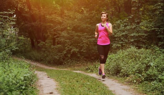 朝の森の小道で走っている若いフィットネス女性。健康に合う生活。