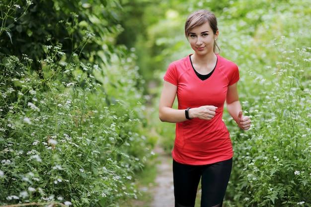 朝の森の小道で走っている若いフィットネス女性。