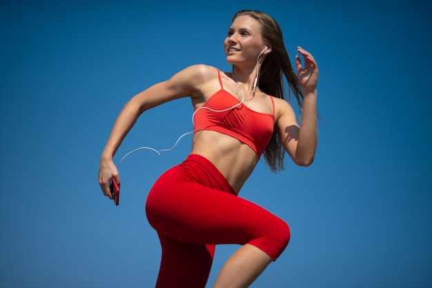Young fitness woman running on sky backround